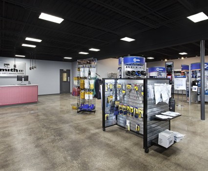 Retail Offices Renovation Merchandise floor with display racks giving plenty of room between for customers to take all options in and not bump with other customers, black and metal display hanging racks