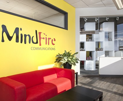 Commercial Office Space Interior Design Medium Sized - the reception area with bold red comfy modern couch and bright yellow wall with MindFire logo; black coffee table and checkered opposite wall