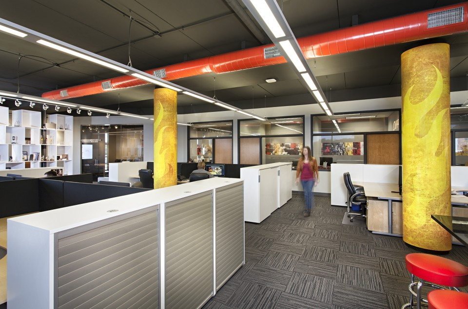 Commercial Office Space Interior Design Medium Space - workspace area with contemporary dividers for work subicles in gray and white texture and gray geometric carpet, strong lighting and contrasting orange painted pipe on ceiling for happy burst or color and yellow beam in center of large workspace - being creative with interior design