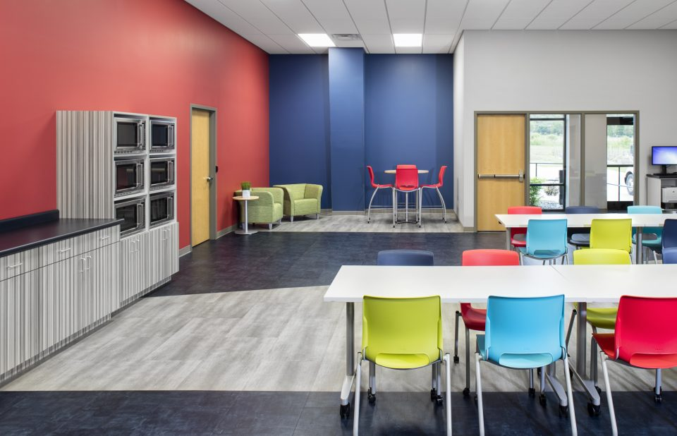 Commercial Office Large Lunch and Break Room - chairs around rectangular and round tables red, bright yellow green and ocean blue. Comfortable green chairs tucked in corner