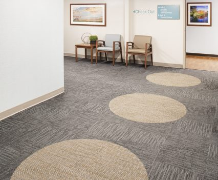 Healthcare interior design waiting room showcasing carpet with big cream colored circles on floor paving a path to follow into the doctor offices