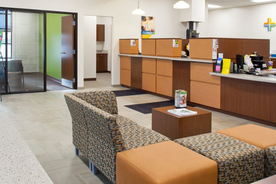 Banking Interior Design with teller view and waiting area - red wood teller cubicles and contemporary seating area