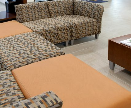 Banking Interior Design Sitting Area with closeup of contemporary seating with brown patterned broken up with orange solid color for a warm fell