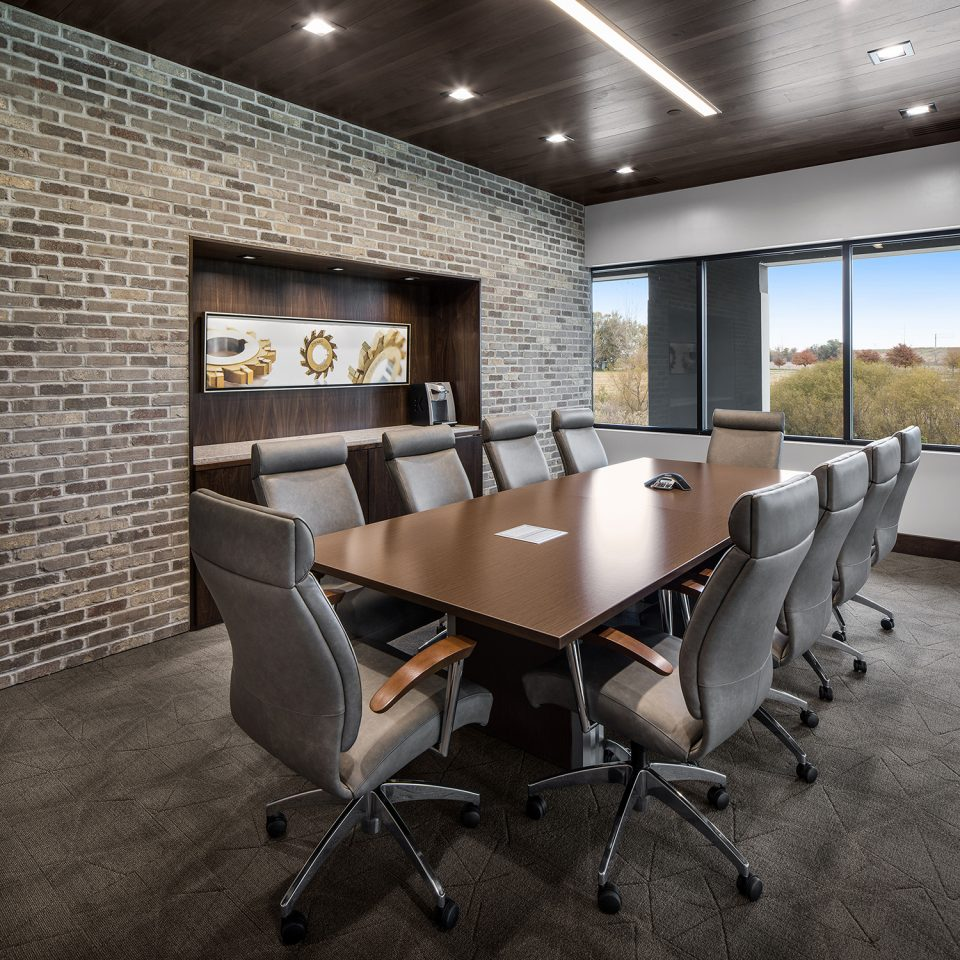 Medium office interior design - brown brick boardroom with deep brown table and ten upholestered brown chairs