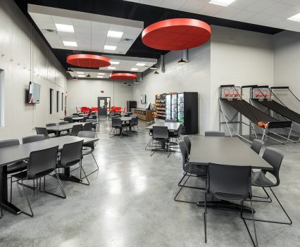 Medium office interior design - dining space with long brown tables and black backed and wire legged chairs. Contemporary orange lights from the ceiling to give function and design.