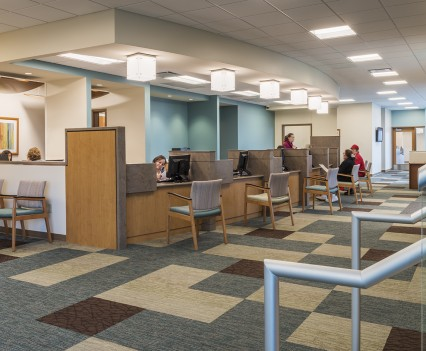 Healthcare Interior Design 1st floor reception with fun checkered carpet with modern twist, cheery sky blue pop in reception area and light wooden desks for receiving patients