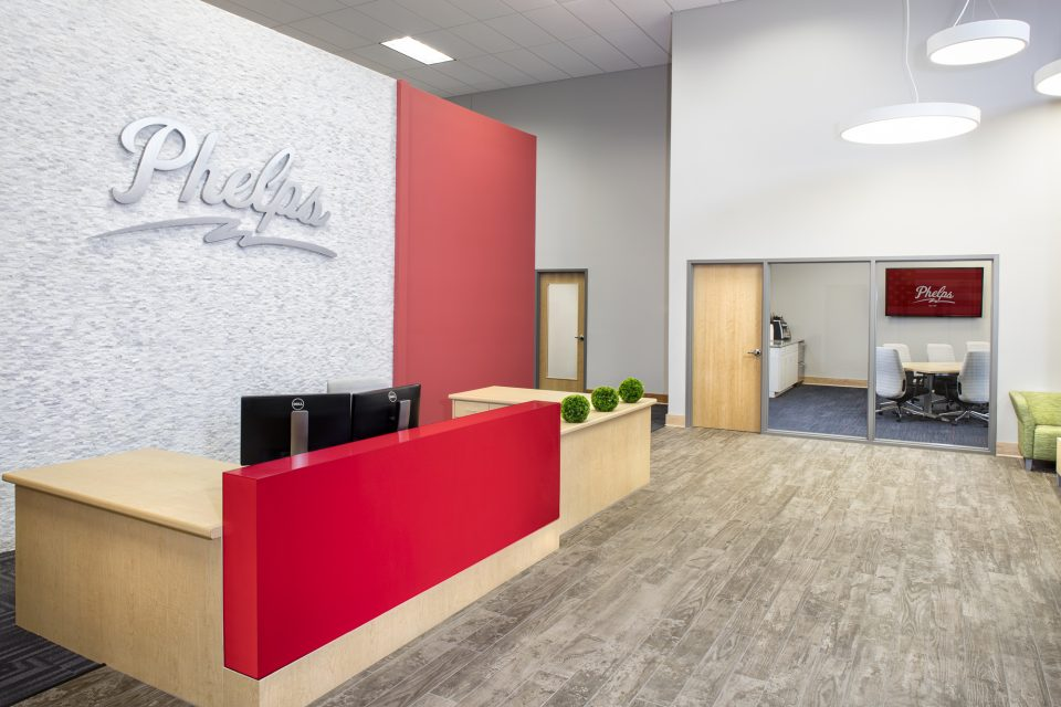 Commercial office large space - front reception office iwth bold red desk and blonde wooden details and giant logo of company Phelps