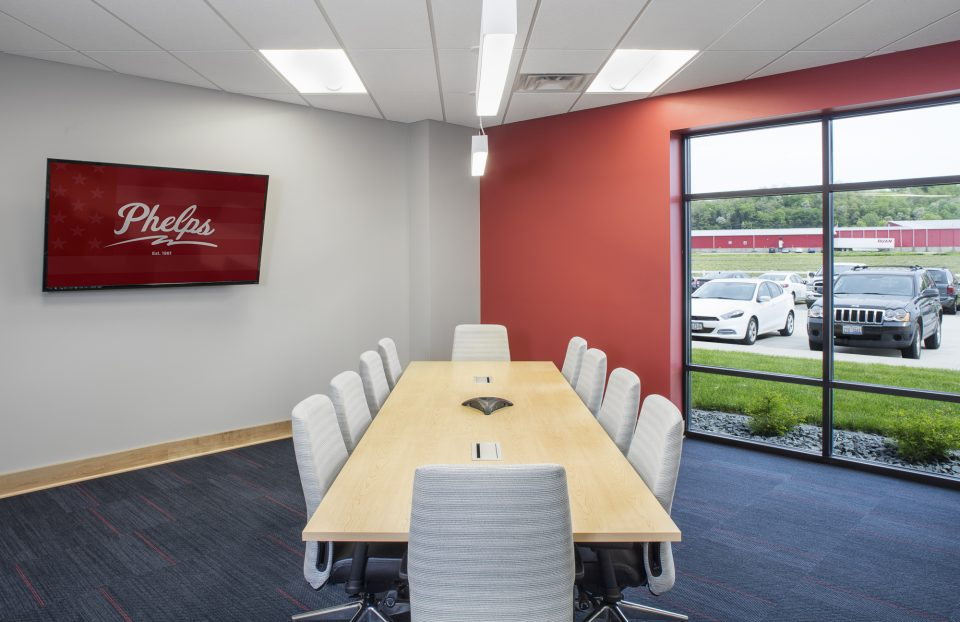 Commercial Office Large Conference Room with 10 off white upholstered chairs and blond long wooden conference table. Walls with light red and white, blue carpet for a fresh feel to the interior designed space