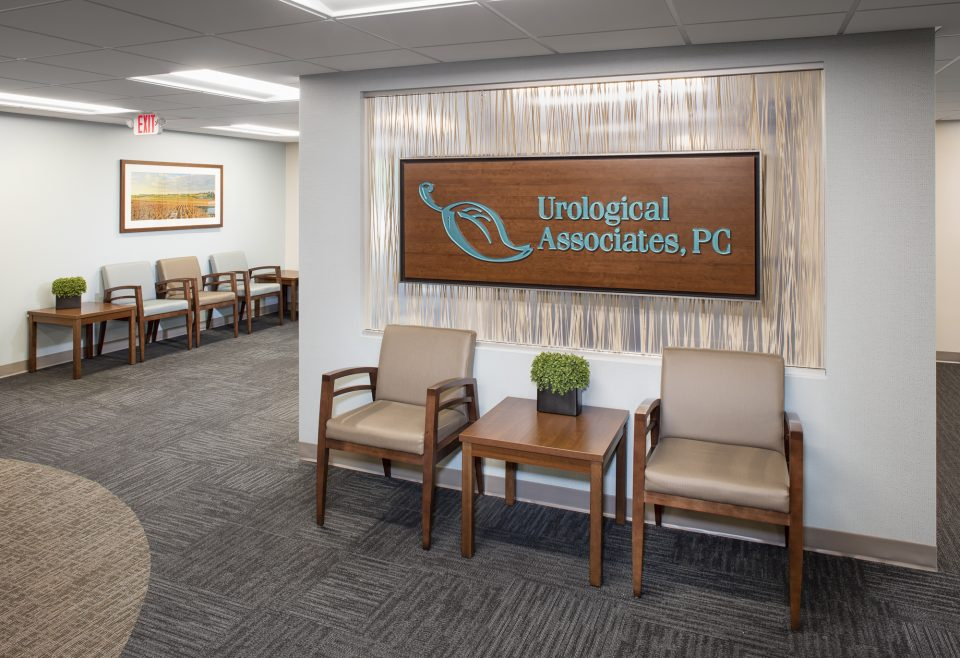Healthcare interior design angle 2 - striking wooden panel with logo, two chairs and coffee table for comfort