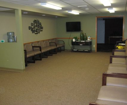 Before Healthcare interior design waiting room - with beige carpet and chairs along wall, artwork that blends in and lack of warmth
