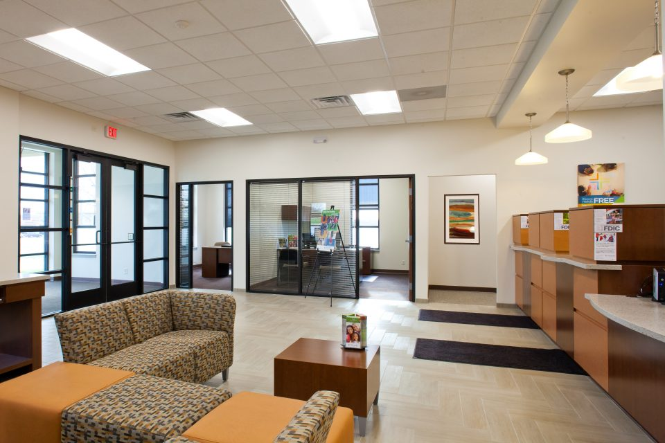 Banking Interior Design Wide Angle View in Waiting Area and Manager Office Angle 2 - pattern brown contemporary seating options with orange weaved in for color splash on seating contemporary square tables and lighting and windows for upbeat modern feel