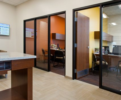 Bank Interior Design Manager Offices with wooden doors and glass wall to see out into waiting area, orange inner wall to brighten up the feel