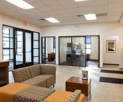 Banking Interior Design Wide Angle View in Waiting Area and Manager Office Angle 1 - pattern brown contemporary seating options with orange weaved in for color splash on seating contemporary square tables and lighting and windows for upbeat modern feel