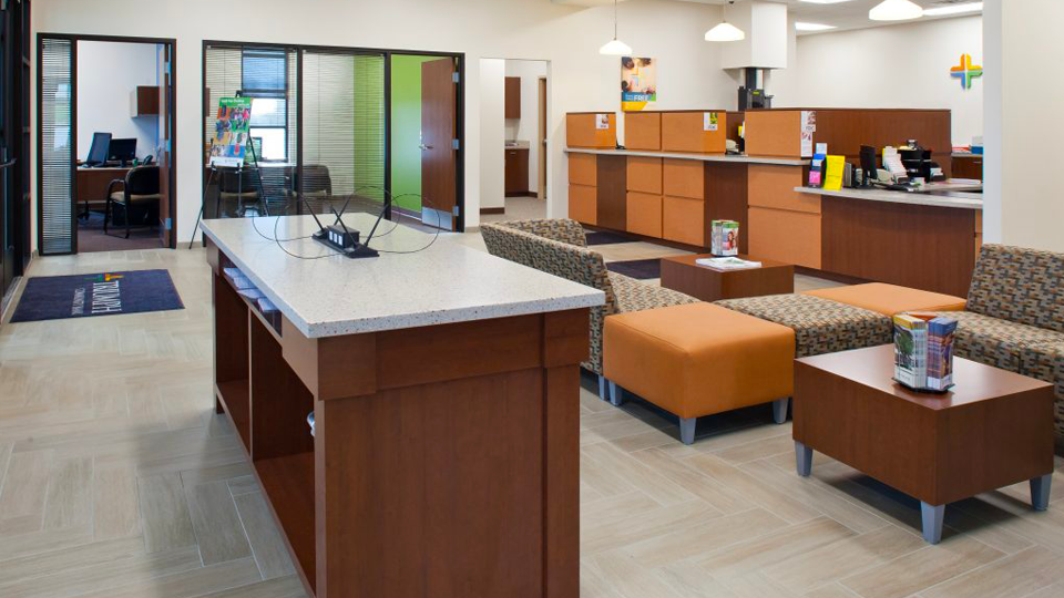 Banking Interior Design with Teller Windows and island for banking forms - redwood teller wood look and brown patterned seating options and orange splash of color