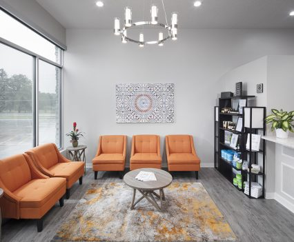 Healthcare retail business reception area with six upholstered sunny orange chairs, brown oval coffee table, modern print rug in golds and browns, candle chandelier and bookcases against one wall