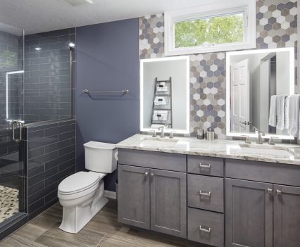 Master Bathroom interior design with gray sink cabinets, gray marbled countertops, octagon patterned wall around two sink mirrors, silver knobs on drawers