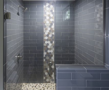 Master bathroom interior design - shower with gray slate brick interior and octagon pattern for outer pillar with gray, brown, white and glass front panels