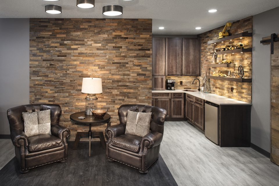 Small Commercial Office Interior Design - in back a long counter for a employee kitchen done in dark browns and gold walls and shelving for displaying decor accessories. In front is a deep leather armed chair with a sitting talbe and lamp and the wall behind it has a multi colored brick pattern in different shades of brown and gold.
