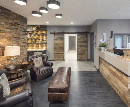 Small Commercial Office Interior Design - gray slate floor with brown leather long footstool or seat and two armed leather chairs with side table and lamp between on the left