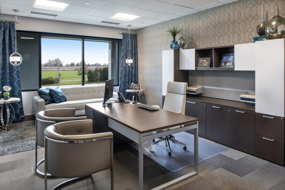 Medium commercial office interior design - clean lined brown desk with tall backed light gray chair and opposite two round backed chairs for guests