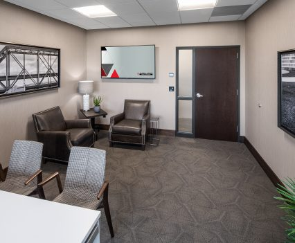 Medium healthcare office interior design - waiting area with open space, brown carpeting and tucked in a corner two upholestered chairs and opposite a table and chairs