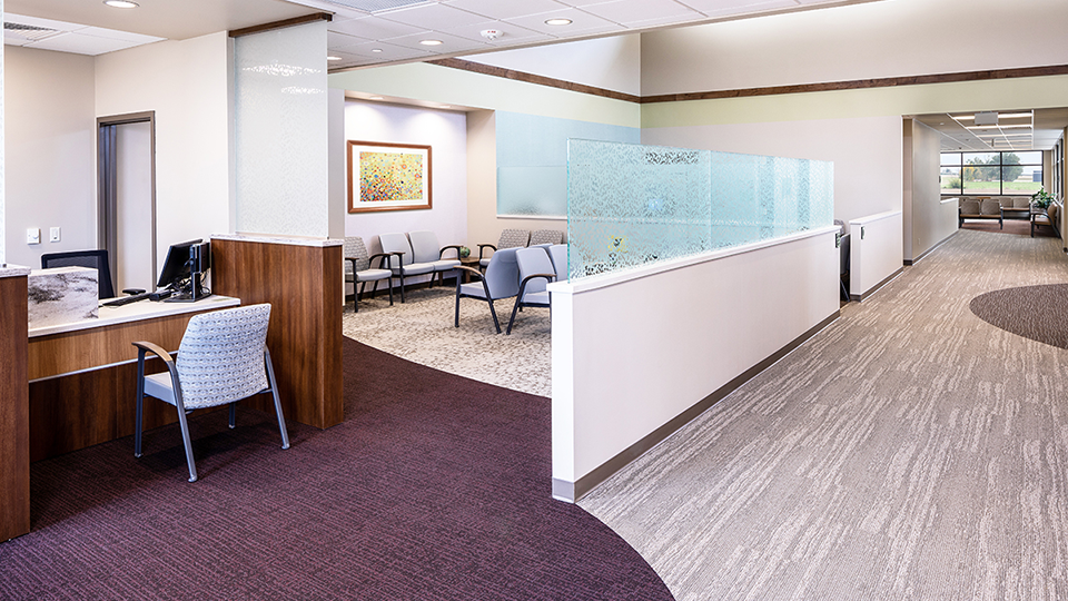 Healthcare facilities' patients Waiting Room that is divided by wall with patterned glass.