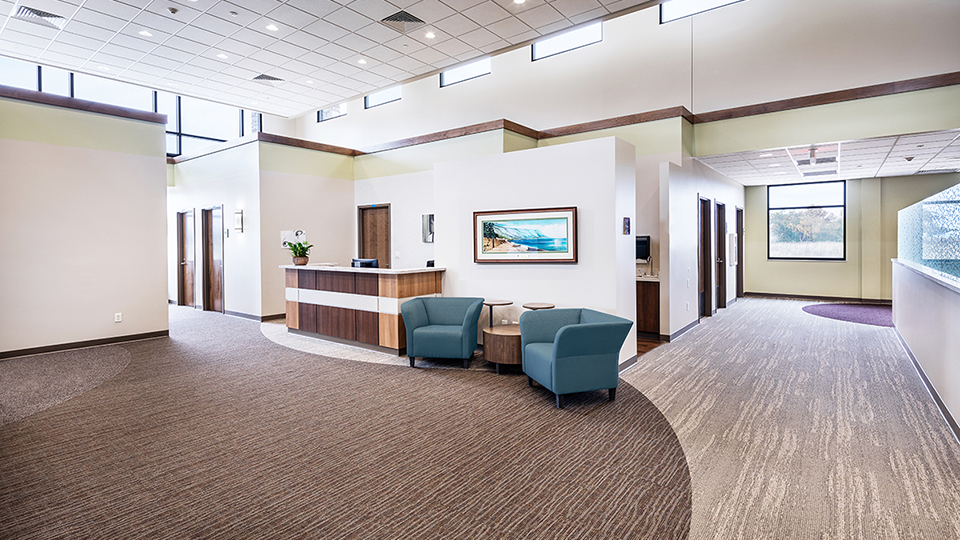 Cozy seating area with teal color chairs and landscape picture in a hospital.